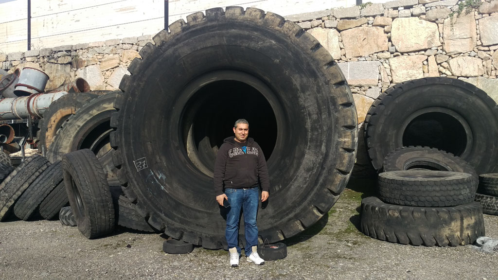 personne se tenant devant un pneu génie civil