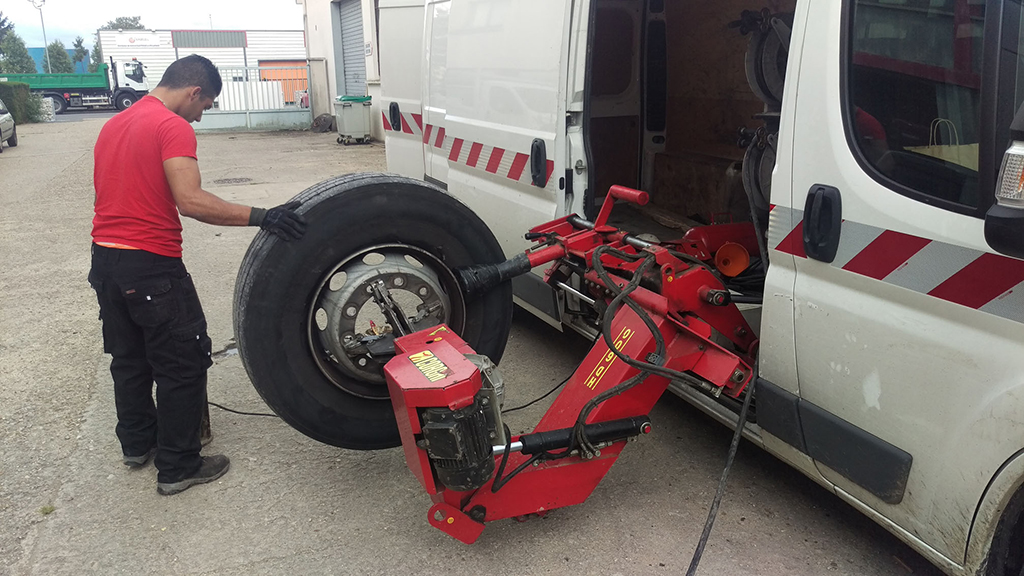 employé vip pneu en train d'ajuster un pneu poids-lourd